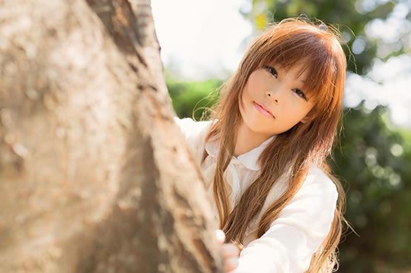 木陰から見る女性