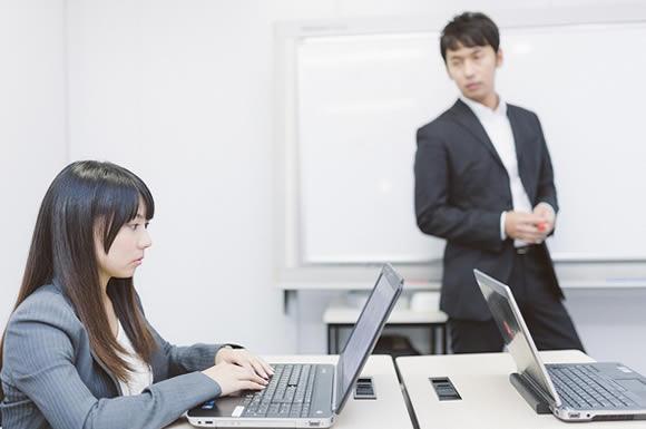 パソコンする女性と見る男